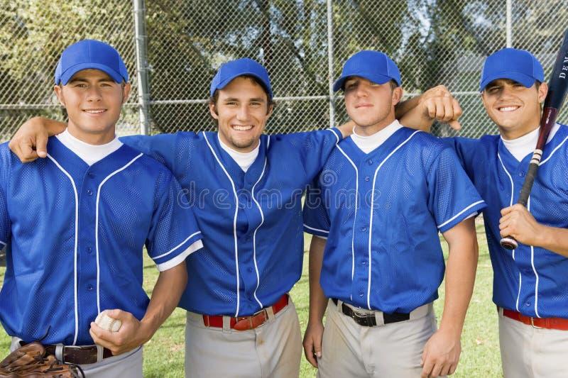 Four baseball team-mates posing on field stock photo