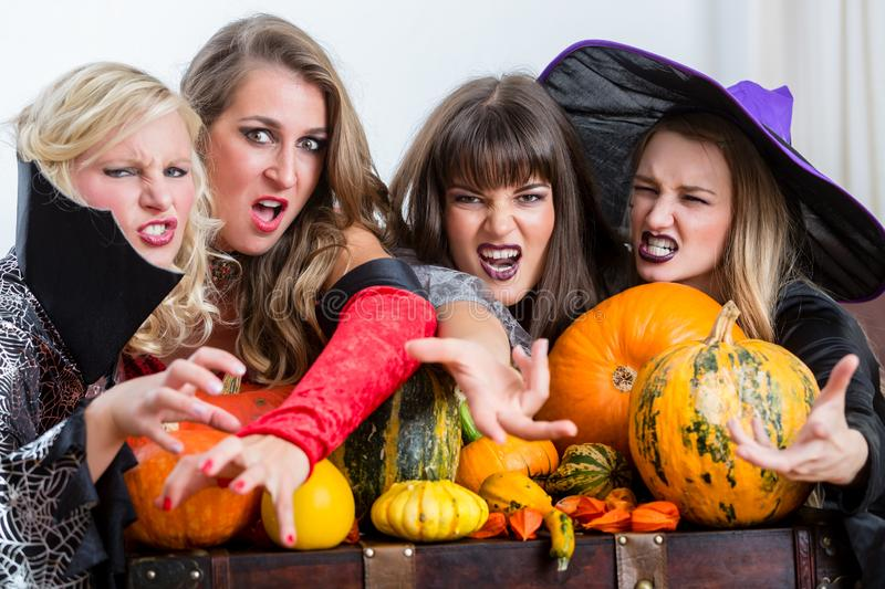 Four beautiful women acting as witches joining their malicious forces stock images