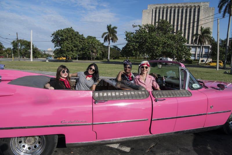 Four beautiful women in Cadillac, Havana, Cuba royalty free stock photo