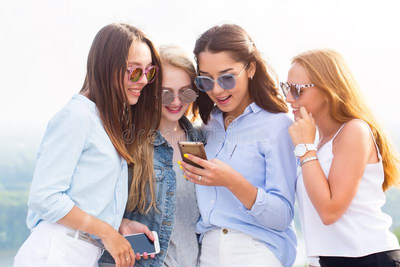 Four beautiful women use a smartphone. The brunette girl shows her friends a photo or video and everyone laughs, rejoices. Chat, t royalty free stock images