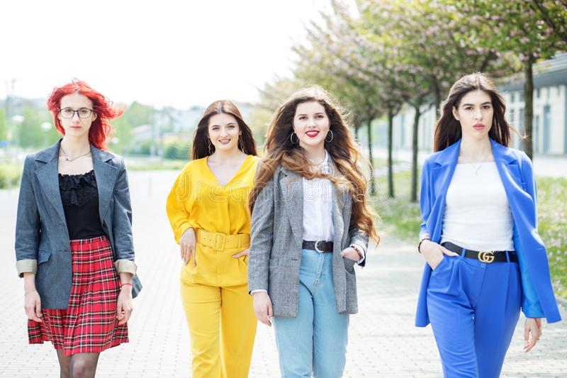 Four beautiful women are walking down the street. Concept of lifestyle, friendship, students royalty free stock photos