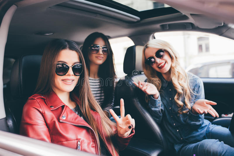 Four beautiful young cheerful women looking at each other with smile while sitting in car. Driving together. Four beautiful young cheerful women looking at each royalty free stock photos