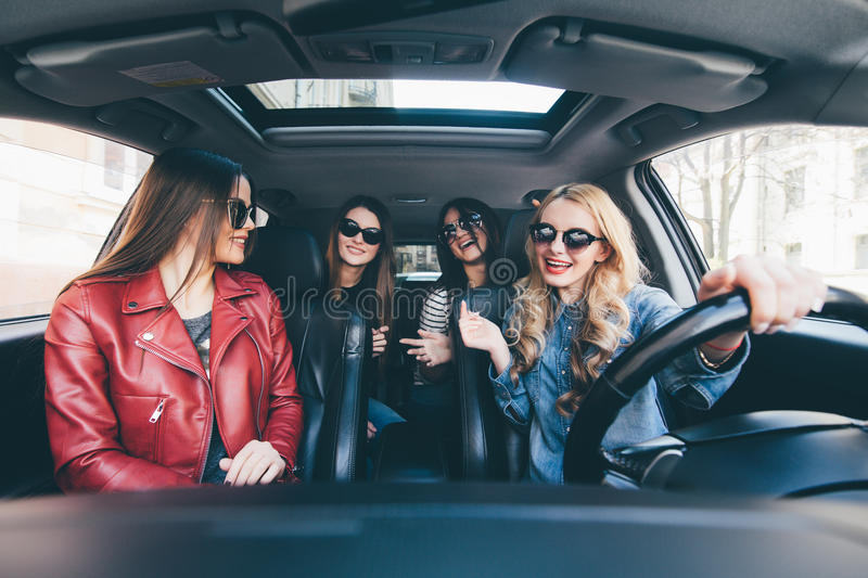 Four beautiful young cheerful women looking happy and playful while sitting in car royalty free stock images