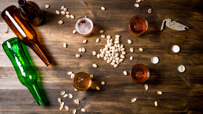 Four Beers with pistachios. Beer background. Four Beers with pistachios on a black wooden table. Top view stock images