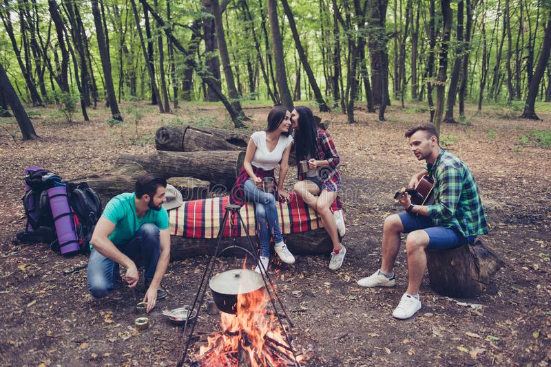 Four best friends are camping, girls are gossipping, boyfriends stock photography