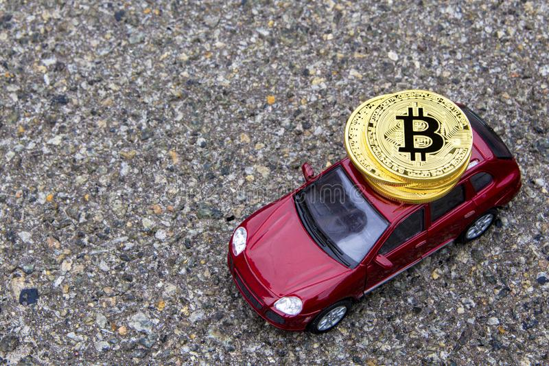 Four Bitcoins on the roof of red crossover car model. view from above with text copy space stock images