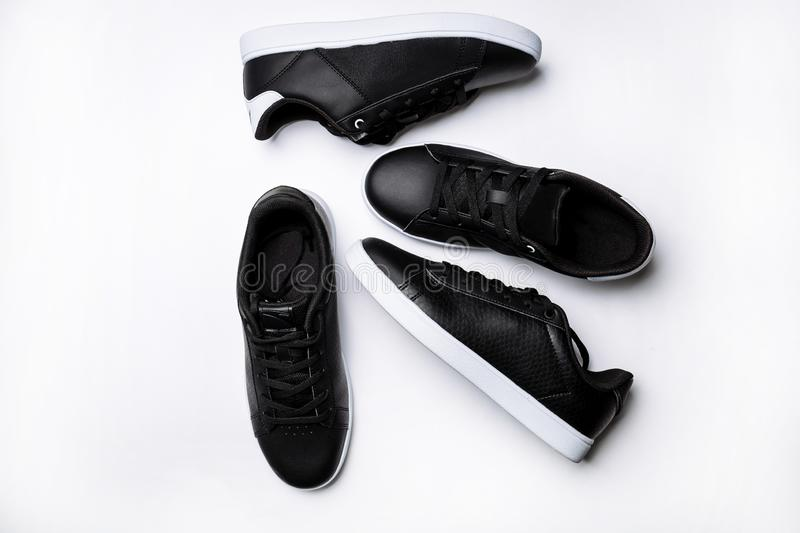 Four black leather sneakers with white sole on a white background royalty free stock image