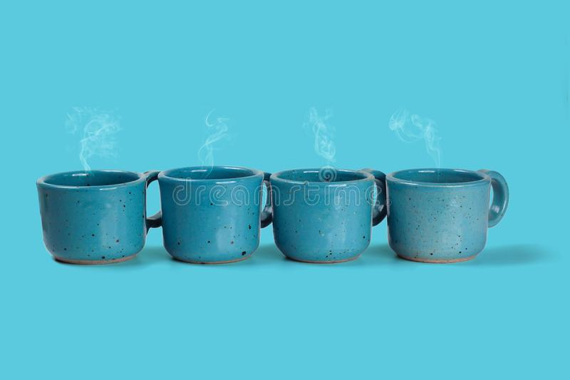 Four blue cups with fresh coffee on blue background. Hot coffee served in light blue cup stock photos