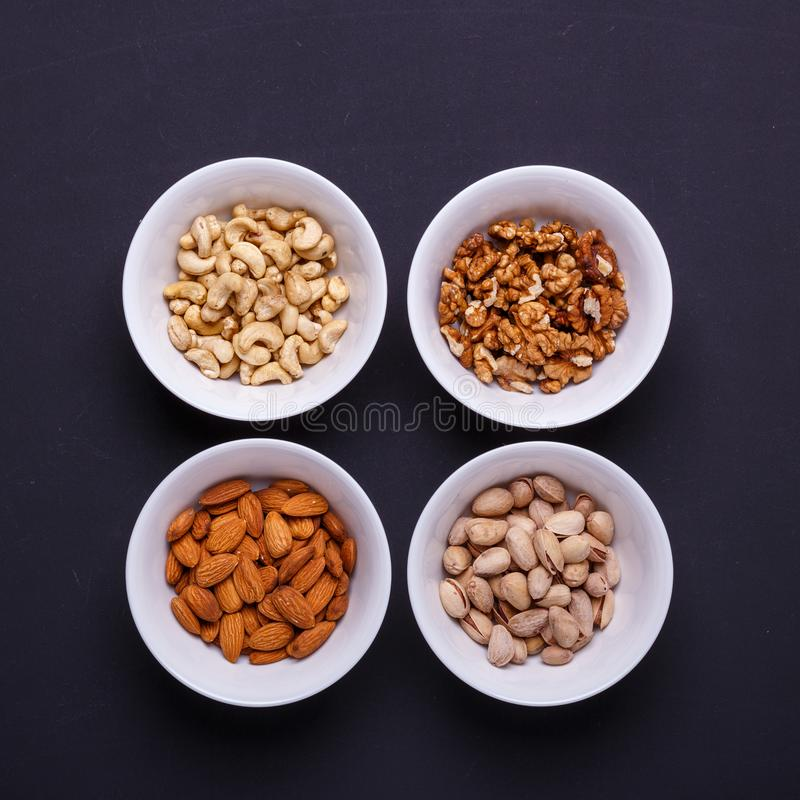 Four bowls with different nuts on a black table stock photos