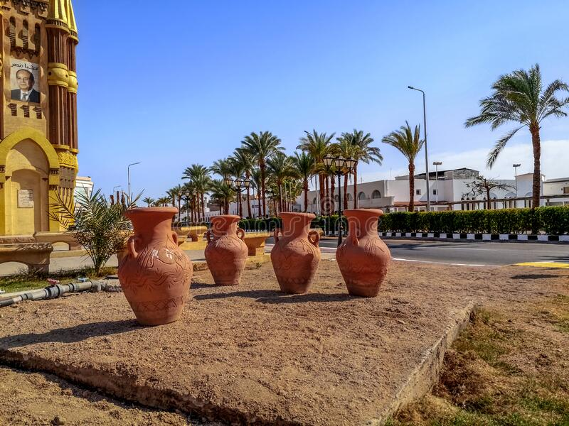 Four brown large clay amphorae stands in the middle of a street in Sharm El Sheikh. Egypt, Sharm El Sheikh - January 17, 2020: Four brown large clay amphorae royalty free stock images