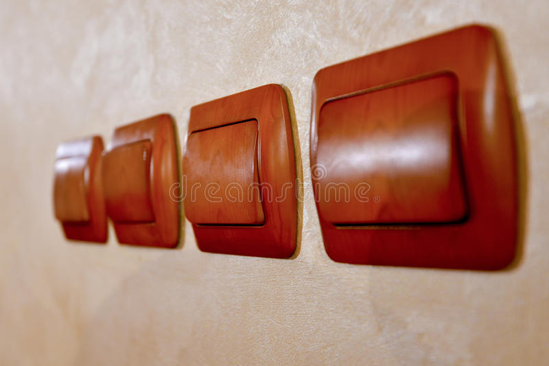 Four brown wooden switches. Next to wall stock image