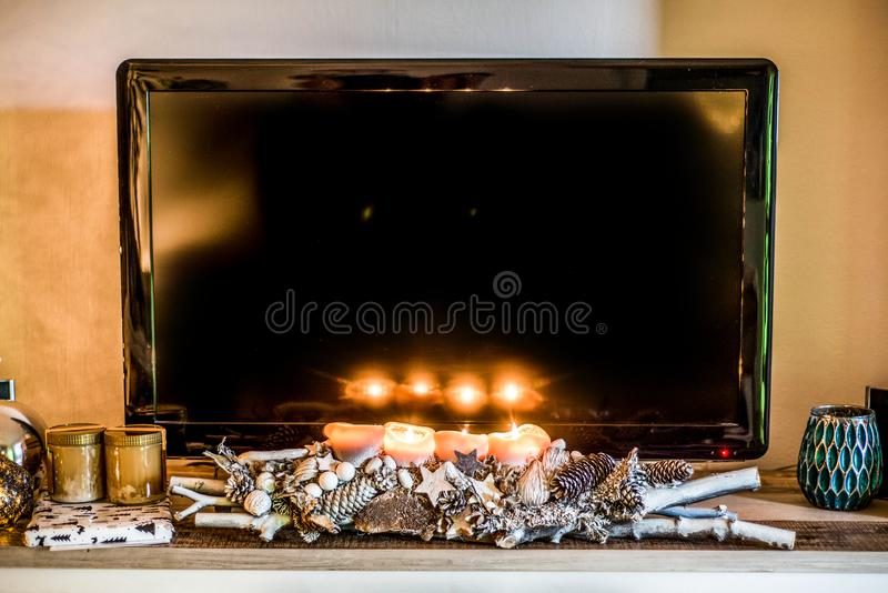 Four burning advent candles, beautiful decorated setup and branches light christmas with textspace in TV in Background royalty free stock photography