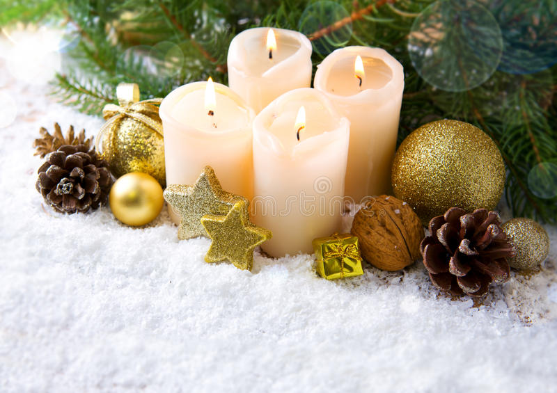 Four burning advent candles and Christmas decoration. Christmas background with four white advent candles and golden decoration royalty free stock photography