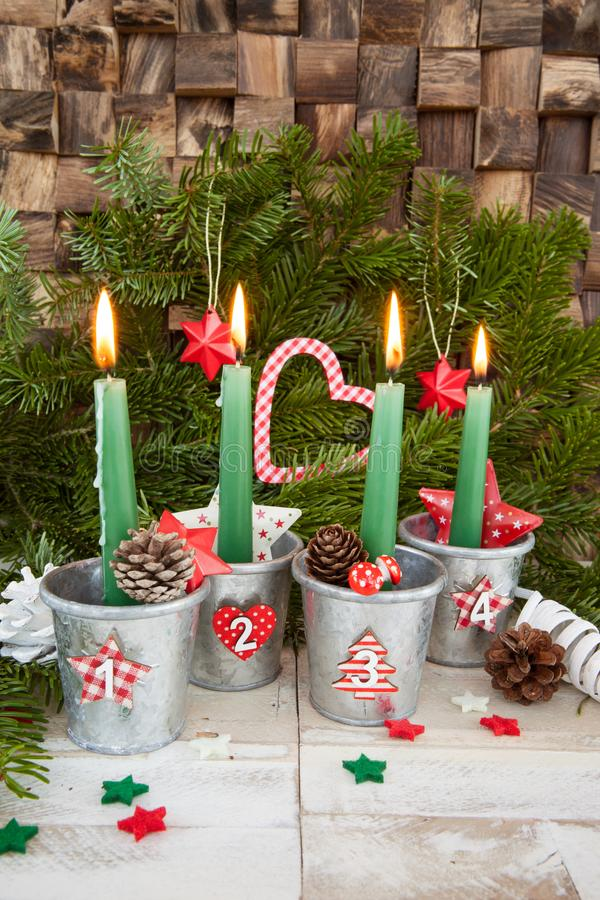 Four advent candles. Four burning advent candles with christmas decorations royalty free stock photography