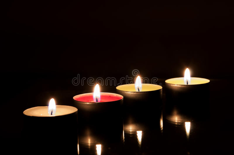 Four burning candles in the dark stock photos