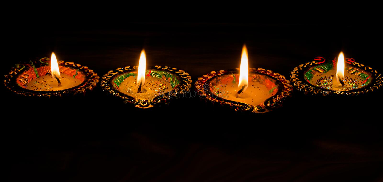 Four burning colorful candles indian style for Diwali celebration on black background. Vertical royalty free stock photos