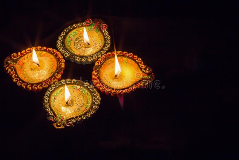 Four burning colorful clay diya lamp Diwali celebration. Black b stock photos