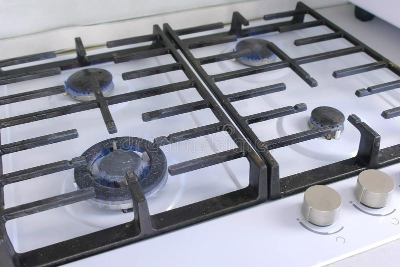 Four burning gas burners from a kitchen gas stove. Gas stove with lattice. Close-up view royalty free stock image