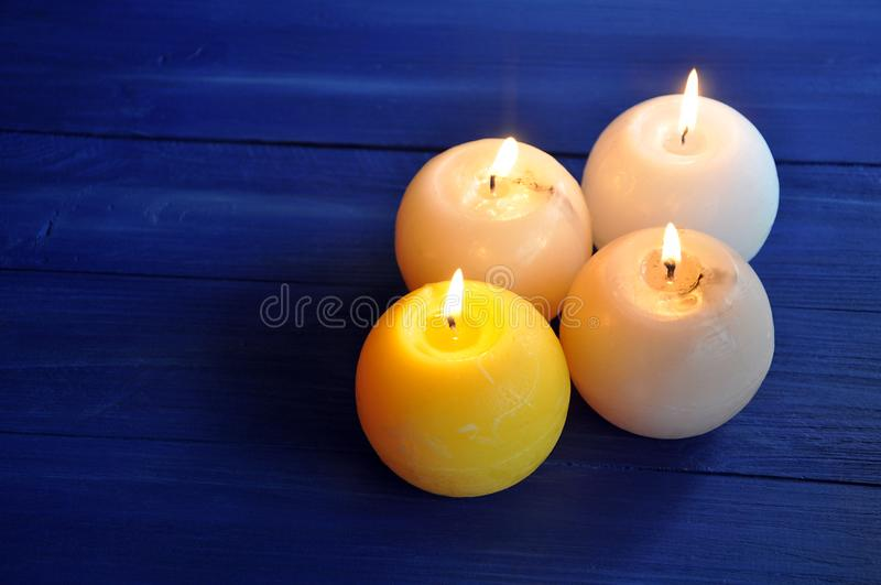 Four burning spherical candles on the table royalty free stock image