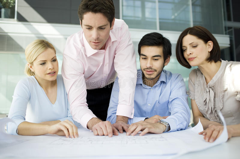 Four business colleagues looking architects plans royalty free stock image
