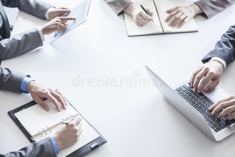 Four business people around a table and during a business meeting, hands only stock image