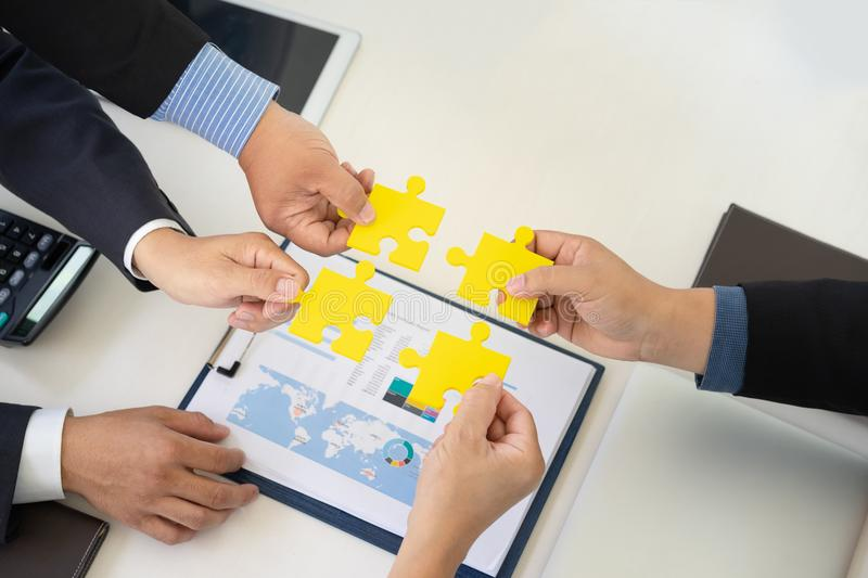 Four business people holding jigsaw puzzle and solving puzzle together. royalty free stock photography