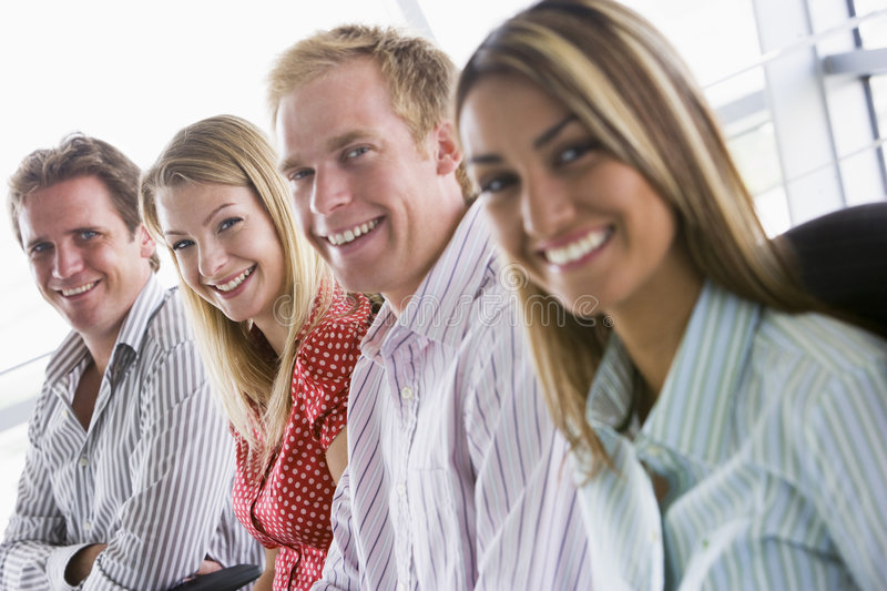 Four business people sitting indoors smiling royalty free stock photos
