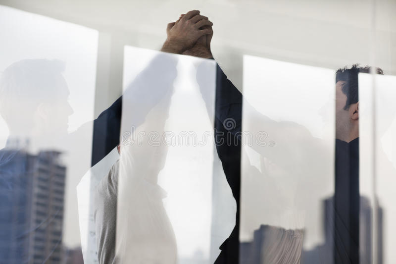 Four business people standing and cheering with hands together on the other side of a glass wall stock photo
