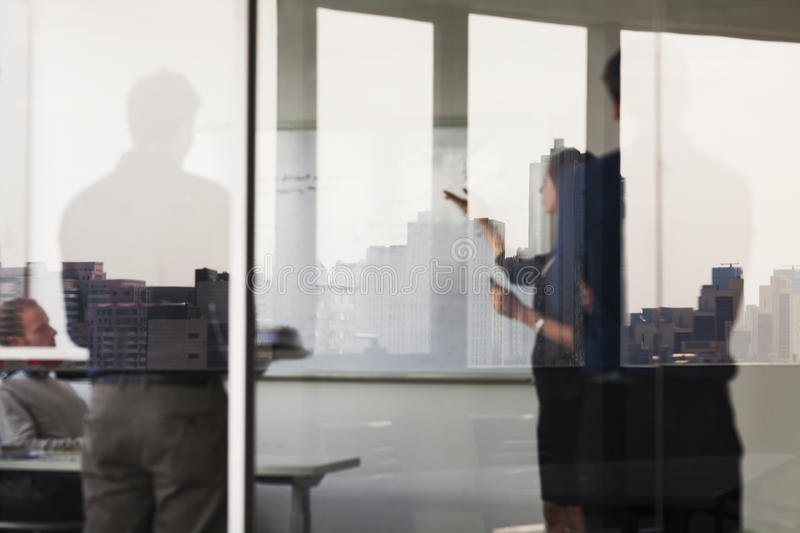 Four business people standing and looking at a white board on the other side of a glass wall royalty free stock image