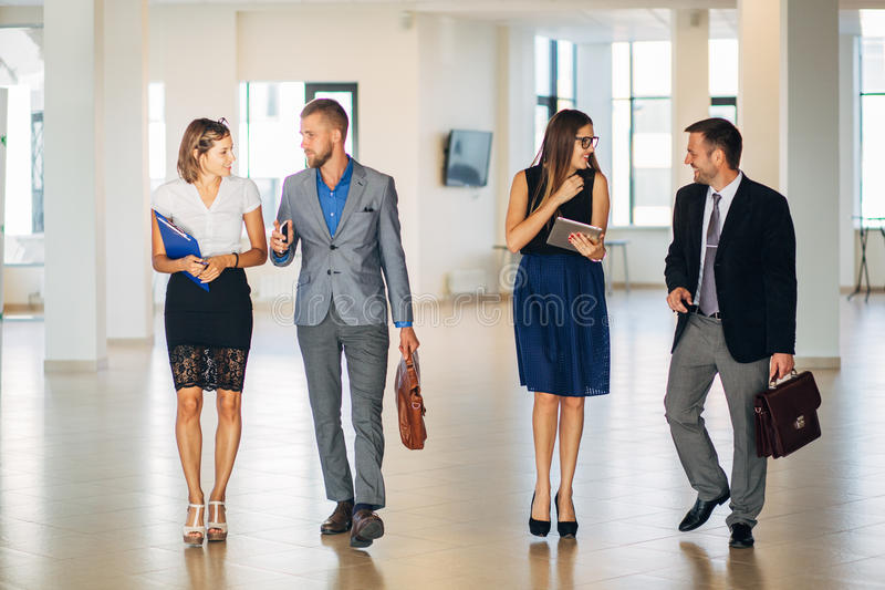 Four business people talking and walking in office lobby stock image