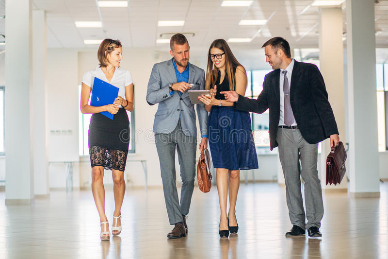 Four business people talking and walking in office lobby. Four business people talking in office modern lobby, slow-mo royalty free stock photography