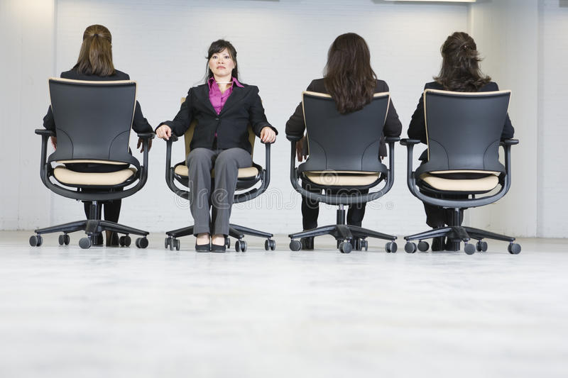 Four business women sitting in office chairs. royalty free stock photos