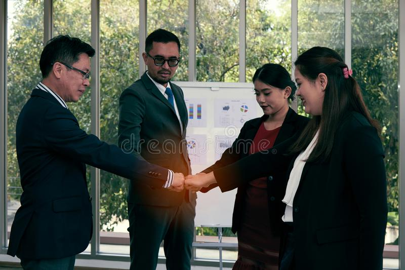 Four businessman and woman standing and touch hands together in meeting room royalty free stock photography