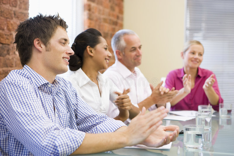 Four Businesspeople In Boardroom Applauding Stock Image