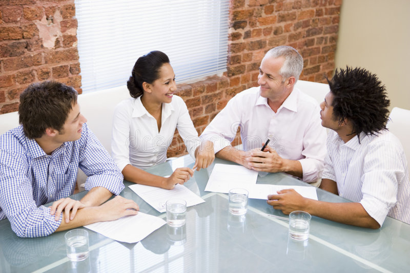 Download Four Businesspeople In Boardroom Smiling Stock Image - Image: 5868541