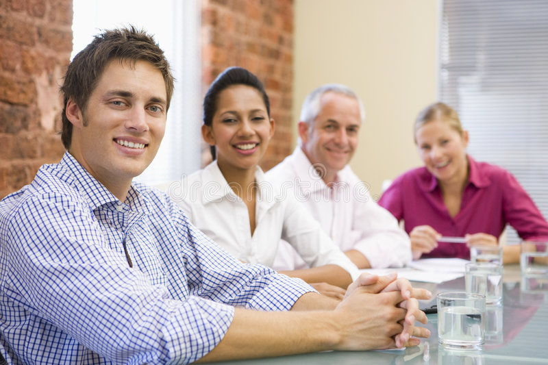 Four businesspeople in boardroom smiling royalty free stock image