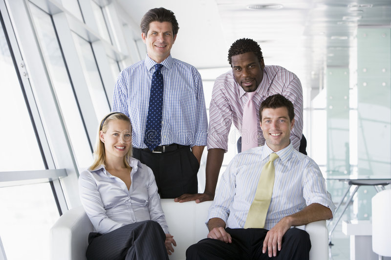 Four businesspeople in office lobby smiling royalty free stock photography