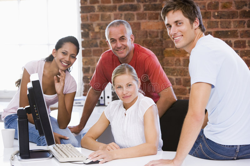 Four businesspeople in office space smiling stock photos