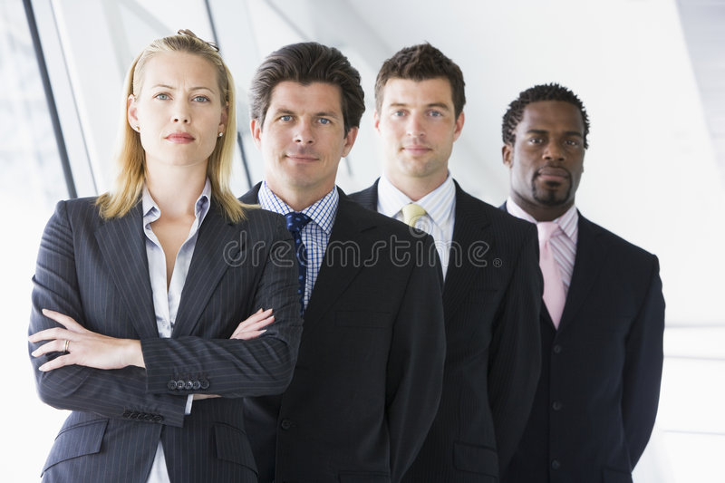 Four businesspeople standing in corridor stock photo