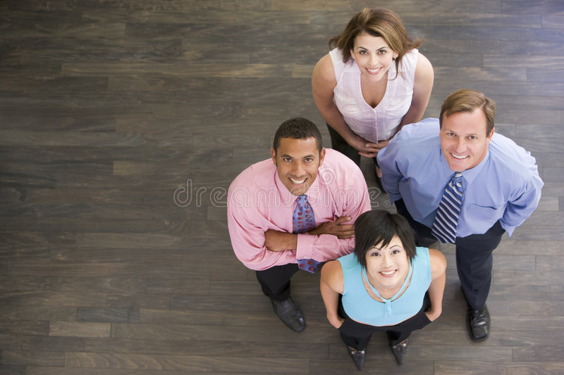 Four businesspeople standing indoors smiling stock photos