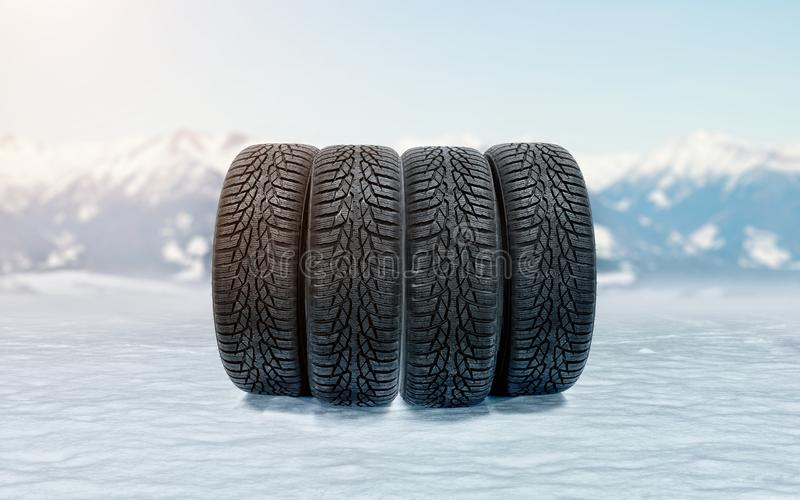 Four car winter tires on an icy surface as a symbol of safe driving during snowy season. Four new winter tires on an icy surface as a symbol of safe driving royalty free stock photos
