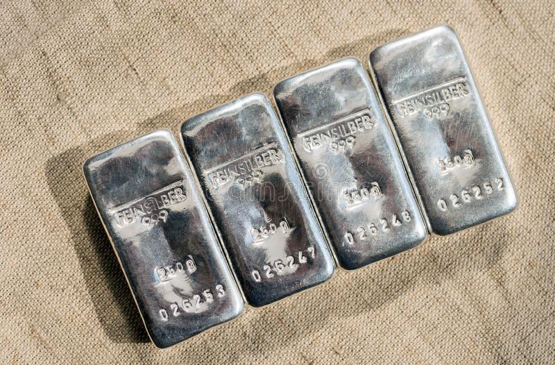 Four cast silver bars against the background of the texture of coarse cloth. Selective focus. feinsilber is fine silver royalty free stock photography