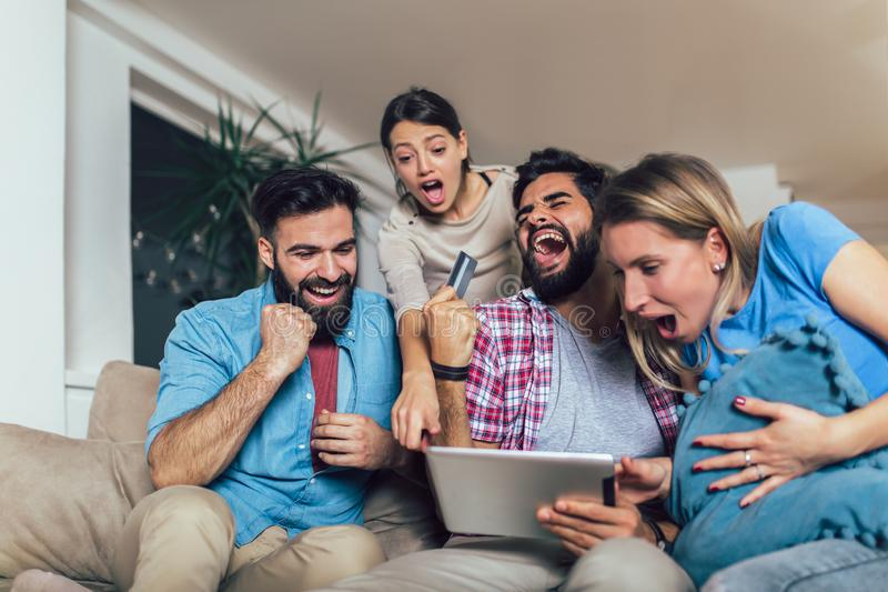 Four casual happy friends laughing shopping online together in a tablet sitting on a sofa in the living room. At home stock photography