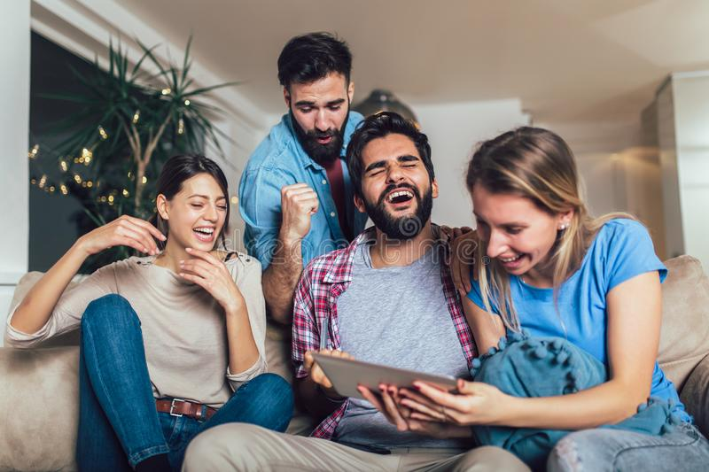 Four casual happy friends laughing shopping online together in a tablet sitting on a sofa in the living room. At home stock image
