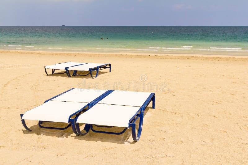 Four chaise longue on a sandy beach stock image