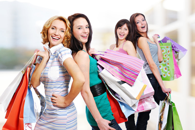 Four cheerful adult girls with purchases stock photo