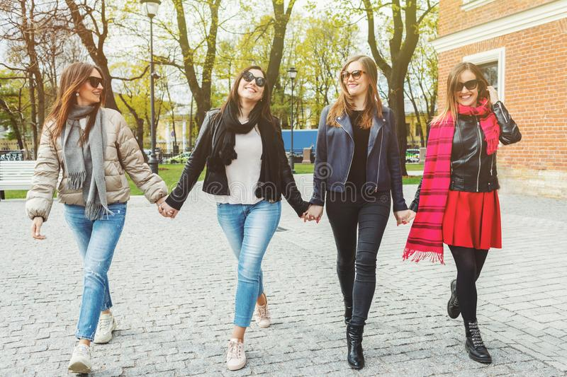 Four cheerful and beautiful women walk, holding hands, on the spring city in sunglasses. The concept of female. Friendship and power stock images