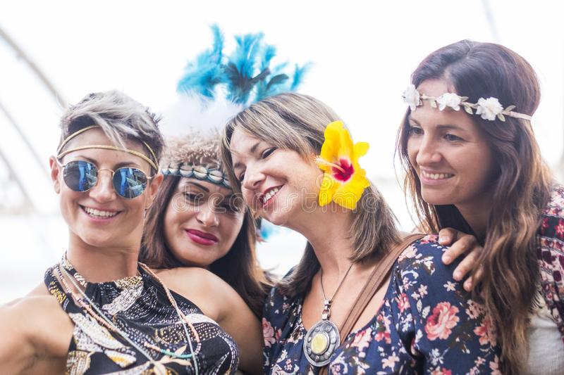 Four cheerful beautiful young women celebrate together and take a selfie picture smiling and having fun in friendship. party royalty free stock images
