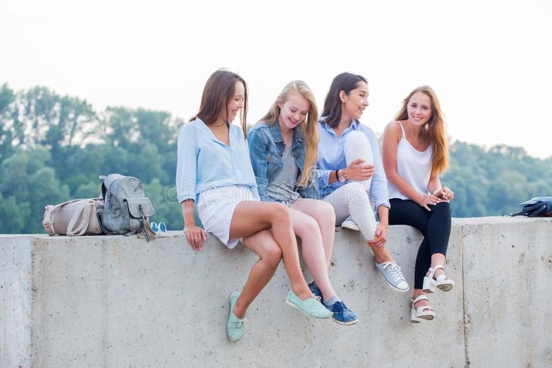 Four cheerful happy women sit in the Park and laugh, talk, smile royalty free stock image