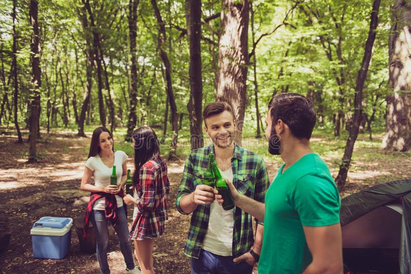 Four cheerful tourists friends are chilling in the summer woods, having beer, good sunny day, campsite royalty free stock image
